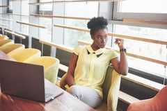 Молодая Афро-американская девушка с темным вьющиеся волосы задумчивым в кафе стоковое изображение