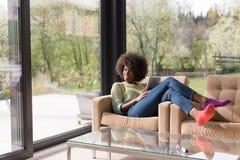 Молодая Афро-американская женщина дома используя цифровую таблетку стоковые изображения rf