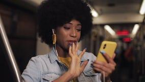 Молодая Афро-американская женщина имея видео- звонок во время ехать публично переход Предпосылка светов города сток-видео
