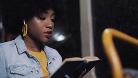 Молодая Афро-американская книга чтения женщины или пассажира сидя публично переход, steadicam сняла ( e сток-видео