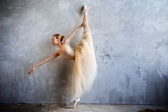 Молодая балерина в золотом покрашенном костюме танцев представляет в студии просторной квартиры Стоковая Фотография RF
