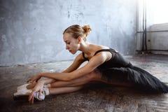 Молодая балерина в черном костюме танцев представляет в студии просторной квартиры Стоковое Изображение