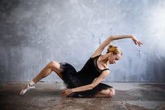 Молодая балерина в черном костюме танцев представляет в студии просторной квартиры Стоковая Фотография RF
