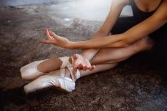 Молодая балерина в черном костюме танцев представляет в студии просторной квартиры Стоковое Изображение RF