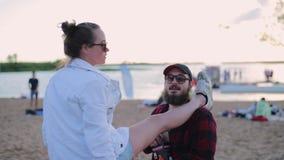 Молодая белая женщина одетая в куртке кладет правую ногу на плечо ее парня акции видеоматериалы