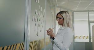 Молодая белокурая бизнес-леди писать некоторые примечания и ручку на стене в офисе акции видеоматериалы