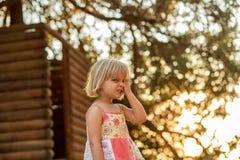 Молодая белокурая девушка ребенка делая сторону внешний с большим деревом на предпосылке Теплый свет захода солнца Trave лета сем Стоковое Изображение