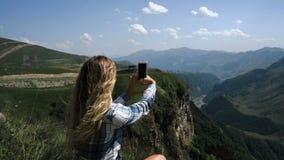 Молодая белокурая девушка сидит на траве на предпосылке гор с рюкзаком и фотографирует горы сток-видео
