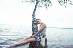 Молодая белокурая женщина вися на дереве березы на береге озера, образе жизни летних каникулов на открытом воздухе стоковые изображения