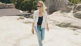 Молодая белокурая женщина в джинсах и белой рубашке и солнечных очках идет близко древнего города высекаенного в утесы видеоматериал