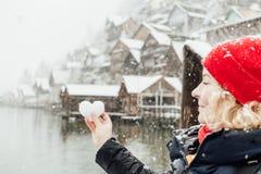 Молодая белокурая женщина в красной шляпе держа сердце сформировала шарик снега перед старой деревней Hallstatt, Австрии стоковая фотография