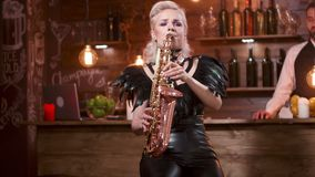 Молодая белокурая женщина в сексуальных кожаных одеждах выполняет песню на саксофоне видеоматериал