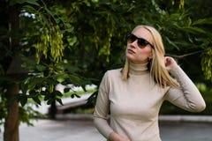 Молодая белокурая женщина в солнечных очках представляя на улице стоковое изображение
