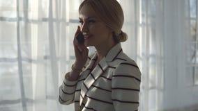 Молодая белокурая женщина говоря на телефоне в окне видеоматериал
