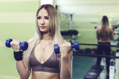 Молодая белокурая женщина делая тренировки с гантелями в СПОРТЗАЛЕ Стоковое Фото