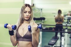 Молодая белокурая женщина делая тренировки с гантелями в СПОРТЗАЛЕ Стоковое Изображение