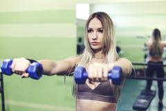 Молодая белокурая женщина делая тренировки с гантелями в СПОРТЗАЛЕ Стоковые Изображения RF