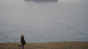 Молодая белокурая женщина идя на берег моря в туманном дне Привлекательный женский пеший туризм в горах самостоятельно сток-видео