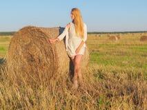 Молодая белокурая женщина около стога сена в пшеничном поле Стоковые Фотографии RF