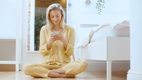 Молодая белокурая женщина печатая по телефону пока сидящ на поле видеоматериал