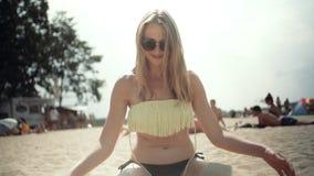 Молодая белокурая женщина сидя на пляже и имея потеху видеоматериал