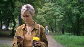 Молодая белокурая женщина с короткой стрижкой идя в парк и печатая на телефоне, держа кофе сток-видео