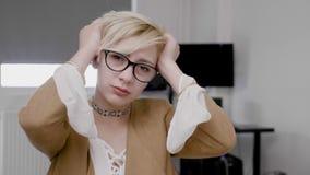 Молодая белокурая коммерсантка страдая от мигрени тереть ее голову вымотанную и усиленную на офисе - акции видеоматериалы