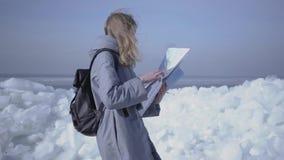 Молодая белокурая милая женщина в теплом положении куртки на леднике проверяя с картой Изумляя природа снежное северного или акции видеоматериалы