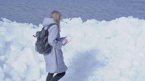 Молодая белокурая милая женщина нося теплое положение куртки на леднике проверяя с картой Изумляя природа снежного акции видеоматериалы