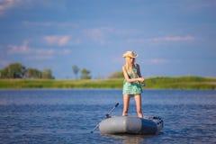 Молодая белокурая рыбная ловля девушки на шлюпке в озере Стоковое Фото