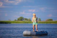Молодая белокурая рыбная ловля девушки на шлюпке в озере Стоковое фото RF