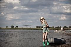 Молодая белокурая рыбная ловля девушки на шлюпке в озере Стоковая Фотография RF