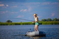Молодая белокурая рыбная ловля девушки на шлюпке Стоковое фото RF