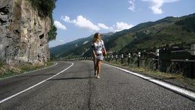 Молодая белокурая туристская девушка в юбке идет на дорогу в горах акции видеоматериалы
