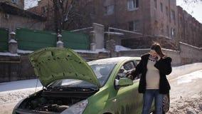 Молодая беременная девушка расстроила ждать помощь около сломленного автомобиля с открытым клобуком говоря на телефоне видеоматериал