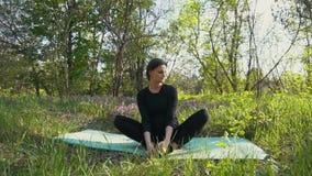 Молодая беременная женщина делая йогу снаружи видеоматериал