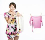 Молодая беременная мать висит вне для того чтобы высушить kidswear стоковые изображения