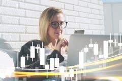 Молодая бизнес-леди в стеклах сидит на компьтер-книжке и использует smartphone В диаграммах переднего плана бинарных вариантов Стоковые Изображения RF