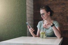 Молодая бизнес-леди в стеклах сидя в кафе на таблице, выпивая напитке и используя цифровое устройство Использование девушки битни Стоковое Фото