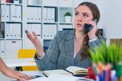 Молодая бизнес-леди говоря на телефоне и в то же время обсуждая с коллегой Слишком много задач стоковые фотографии rf