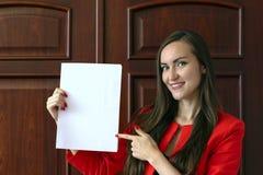 Молодая бизнес-леди держа белый лист для вашего текста стоковые фотографии rf