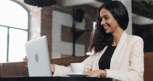 Молодая бизнес-леди заканчивая ее работу на ноутбуке и и ослабленный на современном офисе акции видеоматериалы
