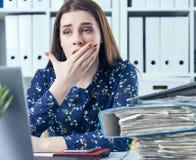 Молодая бизнес-леди зевая на современном столе офиса перед компьтер-книжкой, покрывая ее рот overworked женщина Стоковые Фотографии RF