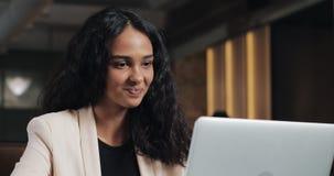 Молодая бизнес-леди имея видео- звонок с ее боссом на ноутбуке на современном офисе Красивая женщина говоря с камерой акции видеоматериалы