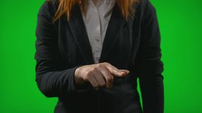 Молодая бизнес-леди ища информацию на виртуальной приборной панели сползая и сигналя с пальцами против зеленого экрана - видеоматериал
