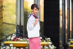 Молодая бизнес-леди моды в белой рубашке и розовой юбке идя в улицу Стоковое фото RF
