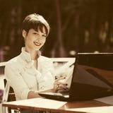 Молодая бизнес-леди моды используя компьтер-книжку на кафе тротуара Стоковые Изображения