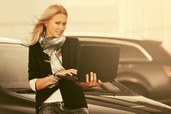 Молодая бизнес-леди моды используя компьтер-книжку рядом с ее автомобилем на автостоянке стоковое фото rf
