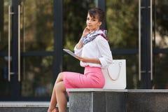 Молодая бизнес-леди моды используя цифровой планшет на офисном здании Стоковое Фото