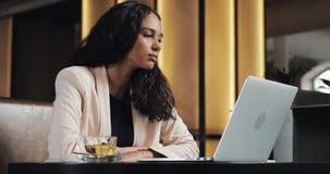 Молодая бизнес-леди наблюдая онлайн урок на ноутбуке Она сидя в кафе и выпивая чае акции видеоматериалы